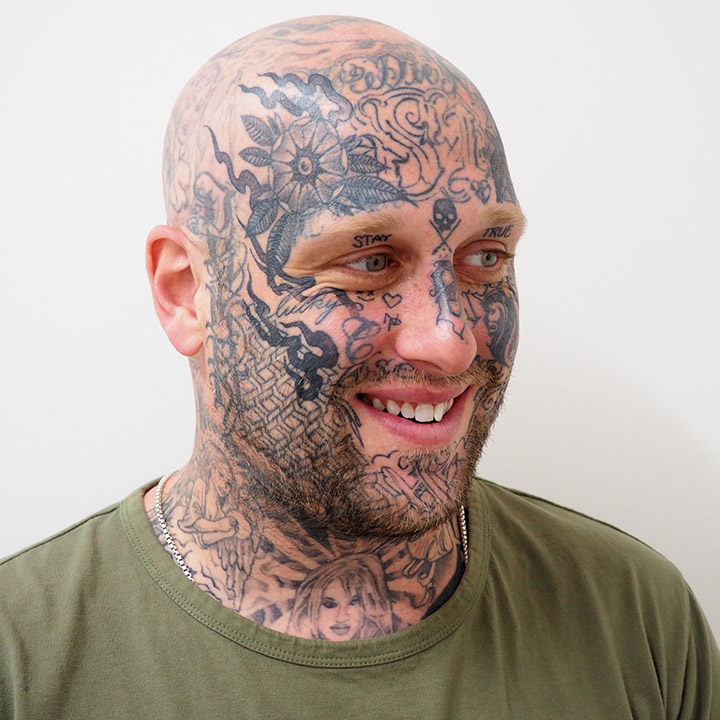 Man with tattoos smiling to show teeth whitening